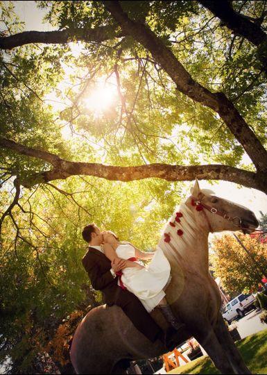 Newlyweds kissing during horseback ride