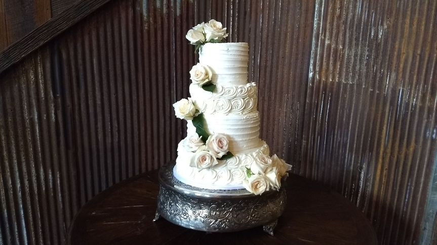 White wedding cake with white flower decorations