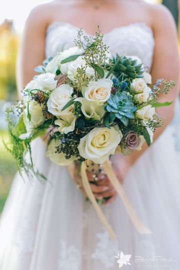 A grandmother's rosary provides a special touch to the handle of this bouquet featuring succulents....