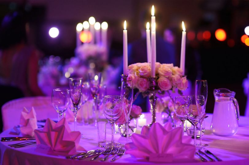 Candlelit table setting with pink lighting