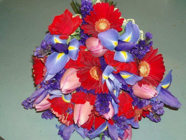 Red gerbera dasies, blue iris, purple status,pink tulips