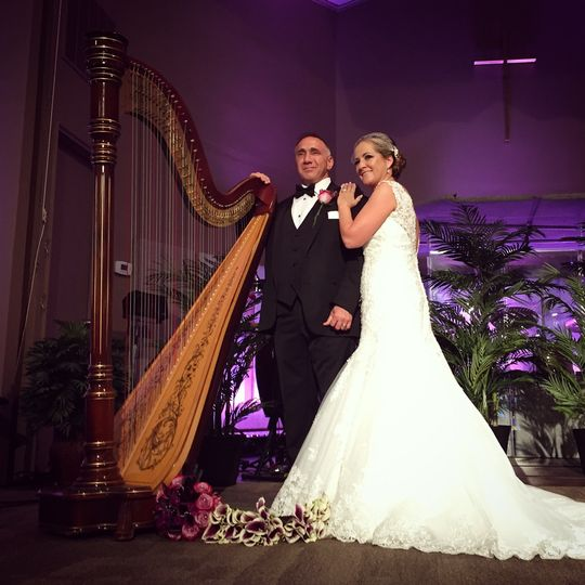 Newlyweds take a photo with the harp