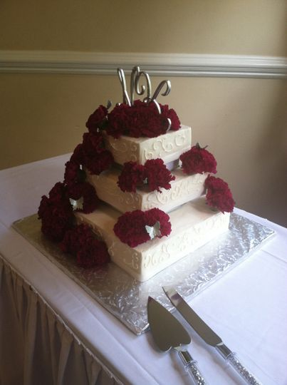 Square cake with filigree design, finish is butter cream, fresh flowers