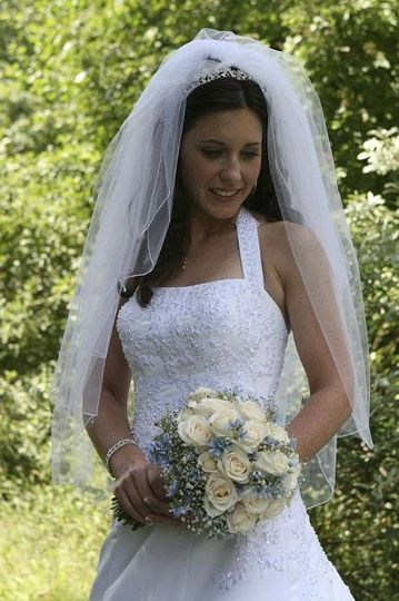 June bride with white roses with blue accent flowers