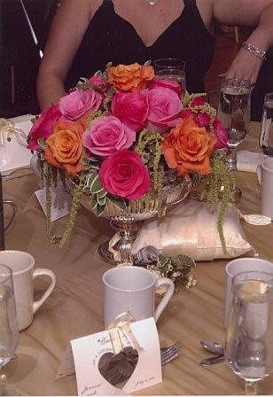 Silver Urn Centerpiece with orange & dark & lighter pink roses, green amaranthus & assorted green &...