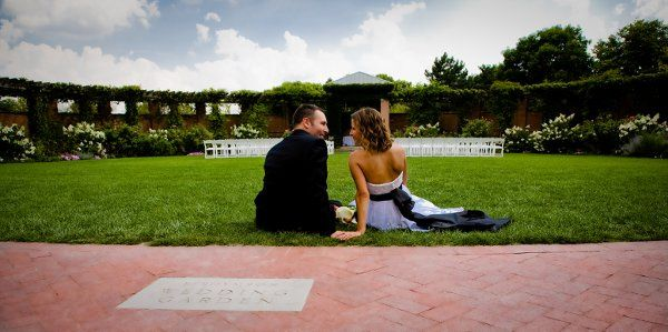 Bride and groom sitting at the edge of the Efroymson Wedding Garden. Photo provided by Astra...