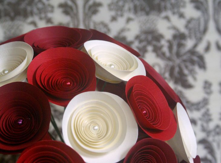 A bouquet in ivory, red hot, and crimson with matching pearl accents.
