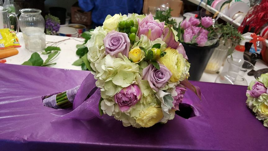 Bridal boutique, with white hydrangea, lavender roses, pink peonies, cream peonies, dusty miller and...