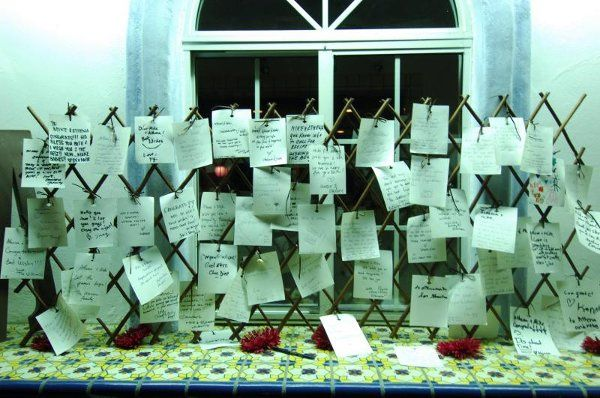 Instead of typical sign-in book, the bride and groom choose to have guests sign cards and tied them...
