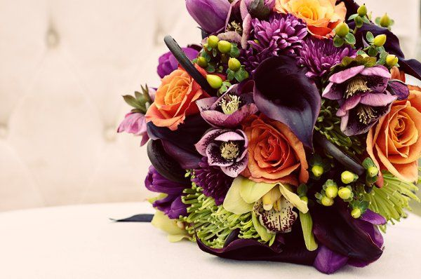 Bridal bouquet with plum calla lilies, orange roses, fern curls, green orchids, purple tulips and...
