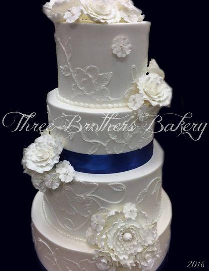 White wedding cake with blue ribbon