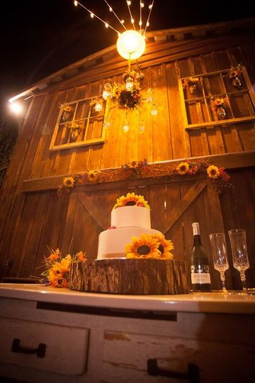 Rustic barn wedding cake with burlap ribbon accent and sunflowers