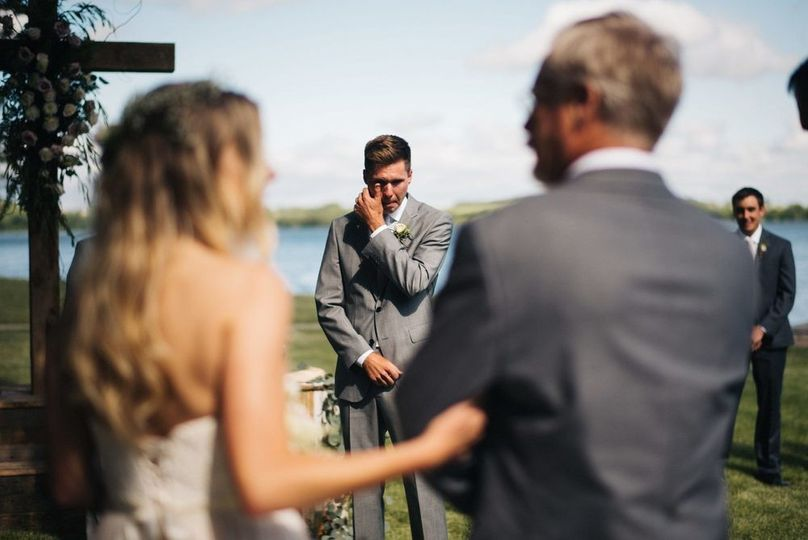 groom crying bride walks down aisle