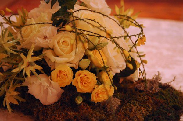 This centerpiece creates a lush spring landscape with yellow roses, vines and moss.
