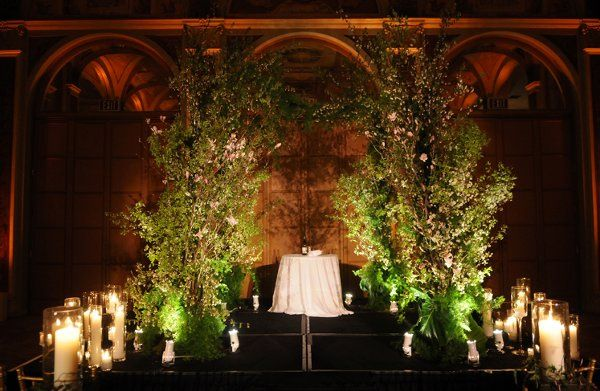 A non-traditional chuppah with flowering spring branches frames the wedding party.  Numerous pillar...