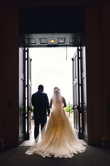 candid moment bride and groom exit church through the front entry flooding with beautiful light 1367 2047 51 1006284 1570780154