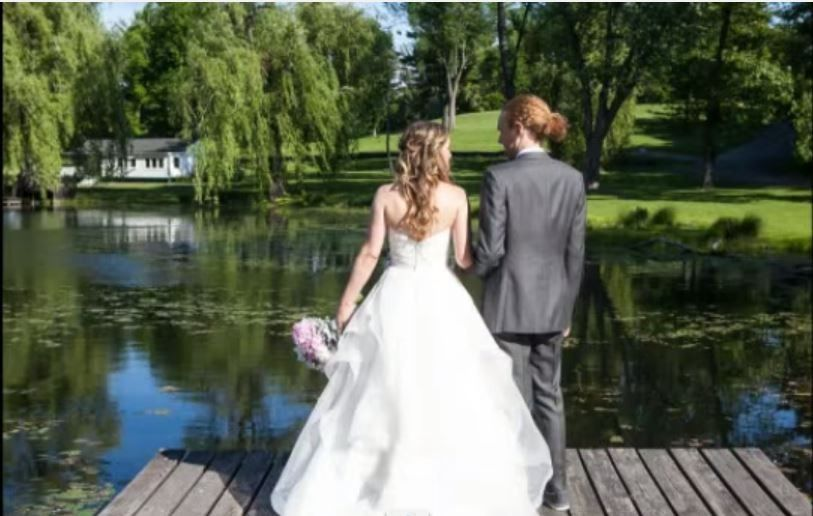 Bride and Groom on the dock of the pond.
