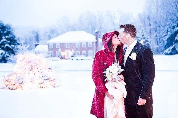 Bride and Groom kiss in the snow outside their ceremony. A Wedding at Private Residence. Photo by...