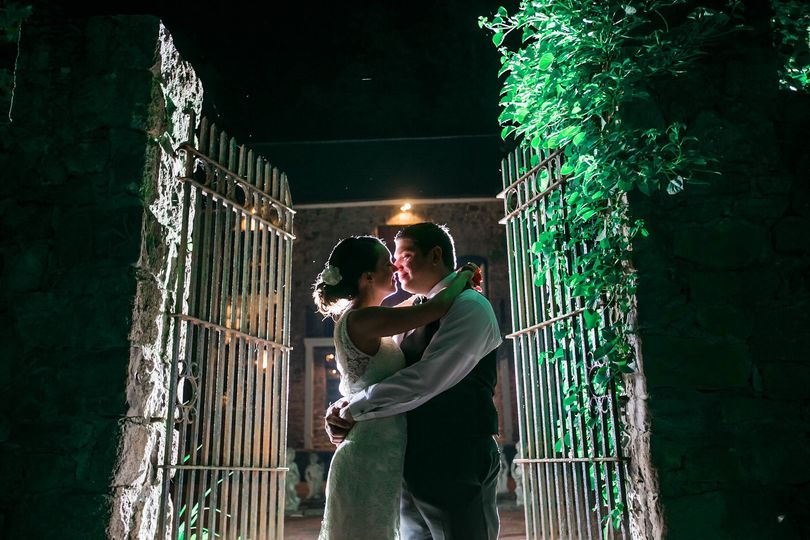 Bride and groom embracing a the gates of a rustic stone and vine gateway at Holly Hedge in New Hope,...