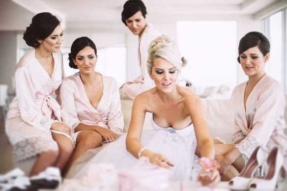 Bridesmaids are wearing the popular blush pink with lace detail Bella Robe from Homebodii.