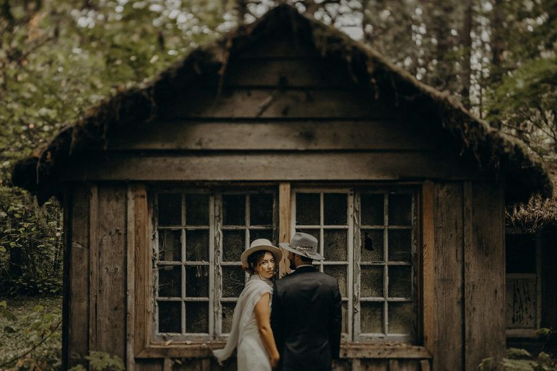 Couple posing beside cabin