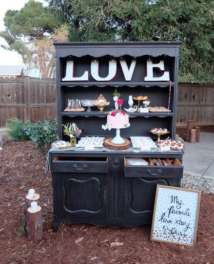 A Vintage hutch for a dessert bar. Marquee lights a redwood cake stand and customized cookies.