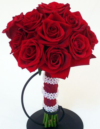"""This all rose hand-tied bouquet features a large cluster of red """"Black Magic"""" Eufloria roses tied..."""