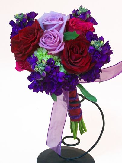 """A hand-tied of purple stock, red and lavendar roses, and green mini-hydrangeas. Approximately 13""""H x..."""