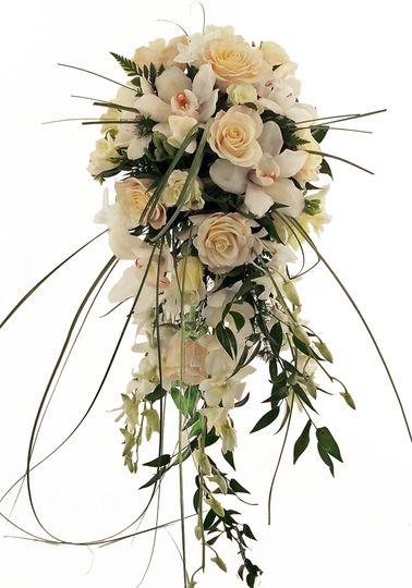 An elegant cascade of white cymbidiums, white dendrobiums, white and cream roses, and white freesia,...