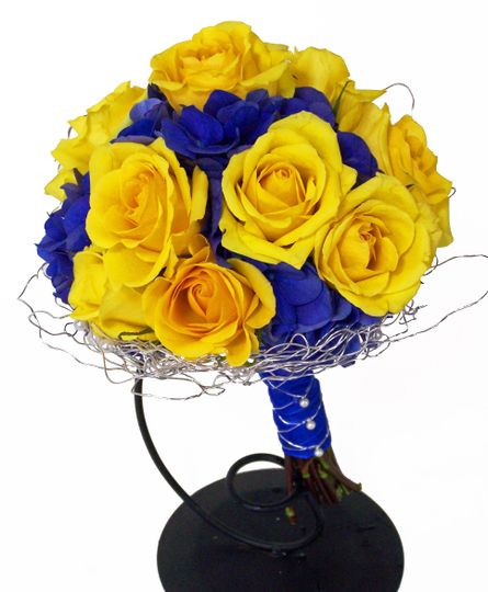 This awesome bouquet is made of yellow roses accented by dark blue hydragea all gathered in a silver...