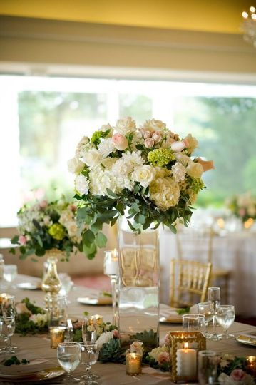 Tall clear square vase with open flower orb of hydrangeas, roses and other wildflowers
