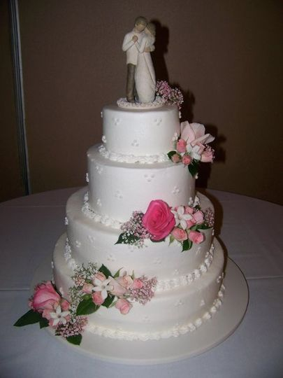 A 4 tier strawberry cake with strawberry filling. Soft pastel flowers adorn the cake in a light...