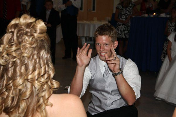 The groom getting ready to get his bride's garter for the garter toss.
