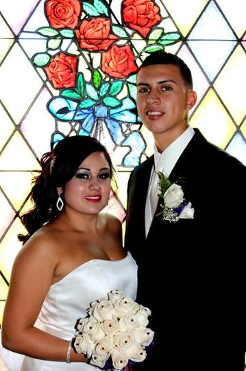Beautiful picture of the bride and groom at the stained glass rose window.