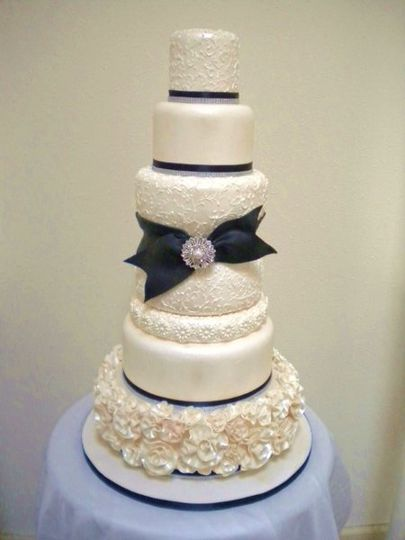 Fondant covered white cake with black and rhinestones ribbons. It has extensive scroll work on the...