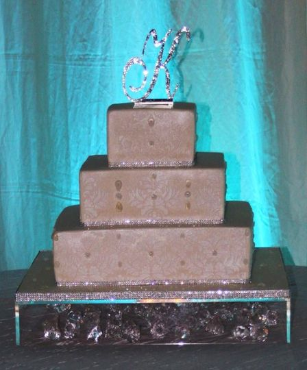 Square fondant wedding cake with stencil work and trimmed with rhinestone ribbon.