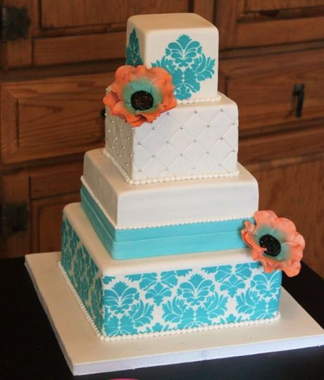 White and teal wedding cake with gumpaste flowers made to match the colors of the wedding.
