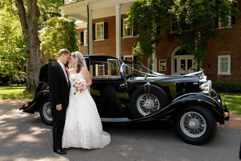 Couple in front of a vintage wedding car