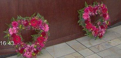 Heart shaped alter arrangements made with fresh flowers including gerbera daisies, roses, poms, and...