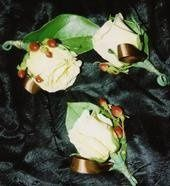 These are matching boutonnieres made up of roses and hypericum berries.