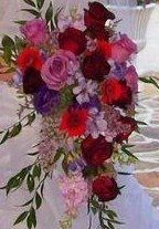This is a wedding bouquet made up of roses, asiatic lilies, gerber daisies, stock, freesia, and...