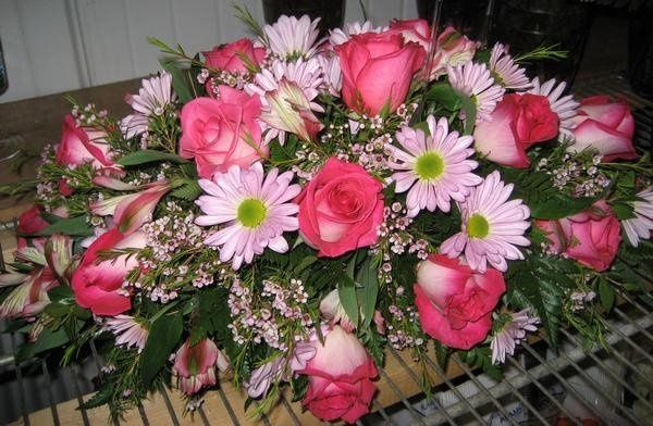 This is a table centerpiece made up of roses, daisies, and alstromeria.
