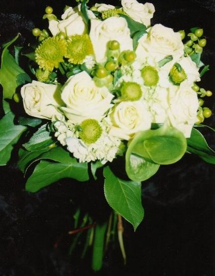 This is a bouquet made up of hypericum berries, hydrangeas, roses, and button poms.