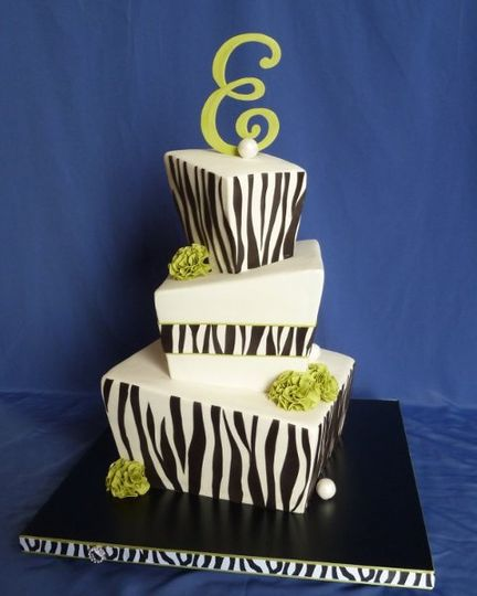 whimsical square wedding cake with zebra stripe patterns and edible green carnations