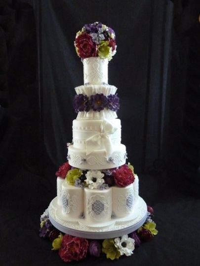 classic elegant white wedding cake with stringwork, fondant draping, and tons of sugar flowers