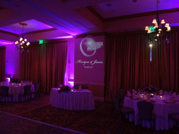 This ballroom is has fuchsia up-lights, and a beautiful glass monogram.