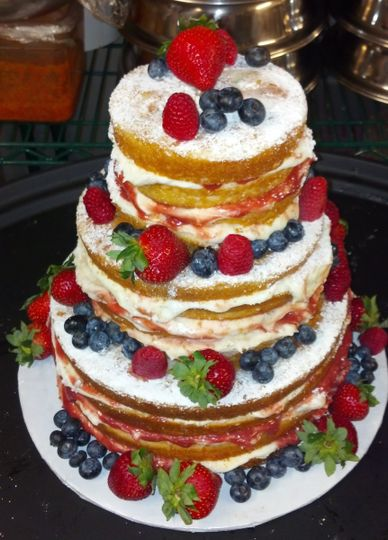 Naked wedding cake with cream cheese and jam filling surrounded with fresh berries