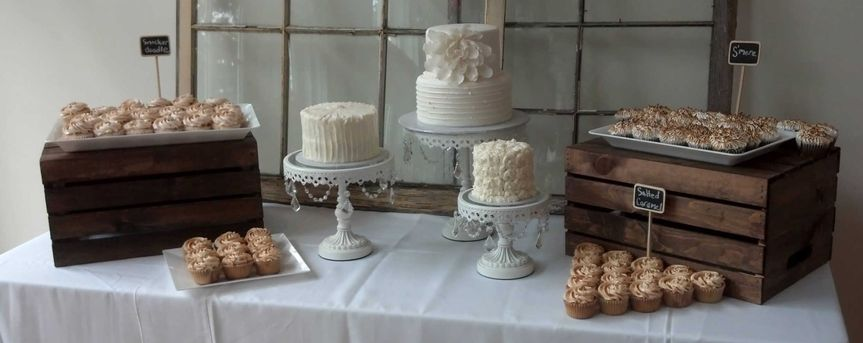 Rustic wedding dessert table.  Cupcakes and 3 small cakes.