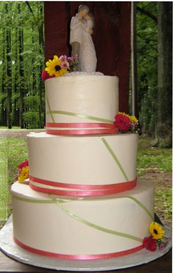 Three tiered wedding cake with ribbon and fresh flowers, set in a state park.