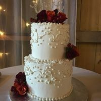 Scroll work on a two tiered wedding cake with fresh roses and winter berries